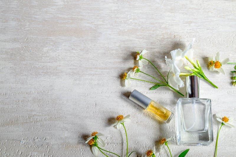 Ένα μπουκάλι του άσπρων αρώματος και των λουλουδιών με τα φύλλα στοκ φωτογραφία με δικαίωμα ελεύθερης χρήσης