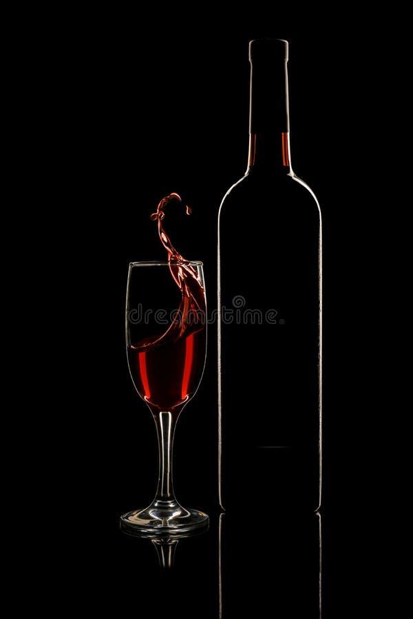 Ένα μπουκάλι του κόκκινου κρασιού και wineglass με την κίνηση του κρασιού στοκ φωτογραφία με δικαίωμα ελεύθερης χρήσης