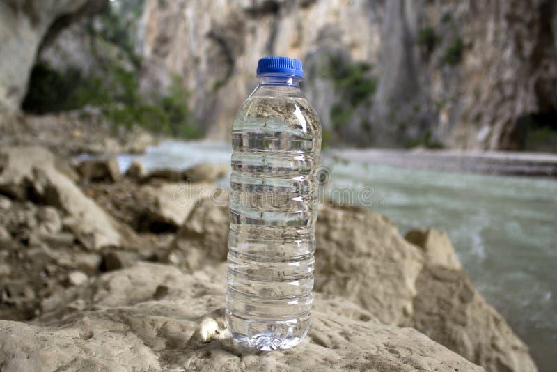 Ένα μπουκάλι του πόσιμου νερού σε ένα καθαρό ρεύμα βουνών στοκ φωτογραφία