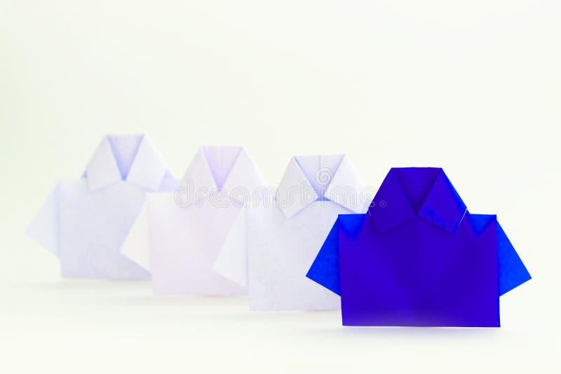 Ένα μπλε μεταξύ του άσπρου εγγράφου πουκάμισων origami, μοναδική προσωπικότητα στοκ εικόνα