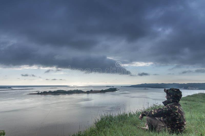 Ένα μόνο άτομο στην όχθη ποταμού συννεφιασμένος τοπίων Ποταμός στοκ φωτογραφίες