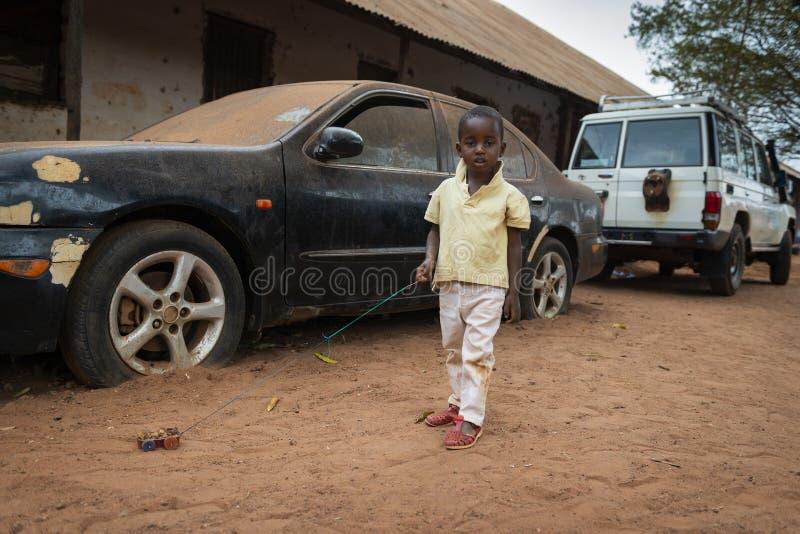 Ένα νέο αγόρι που παίζει με ένα μόνος-γίνοντα αυτοκίνητο παιχνιδιών στη γειτονιά Missira στην πόλη του Μπισσάου στοκ εικόνες