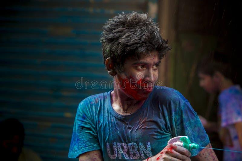 Ένα νέο αγόρι που ψεκάζει το χρωματισμένο νερό το holi το φεστιβάλ των χρωμάτων σε Shakhari bazar, Dhaka, Μπανγκλαντές στοκ φωτογραφία