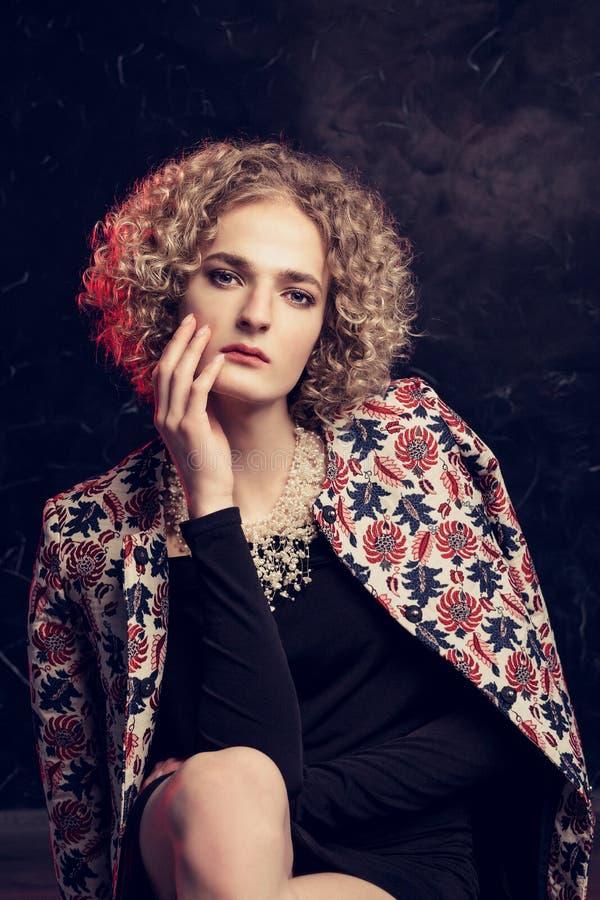 Ένα νέο αρσενικό ξανθό androgyn στην εικόνα μιας όμορφης γυναίκας κάθεται δυστυχώς την κλίση στο βραχίονά της, με ένα θερινό παλτ στοκ εικόνες