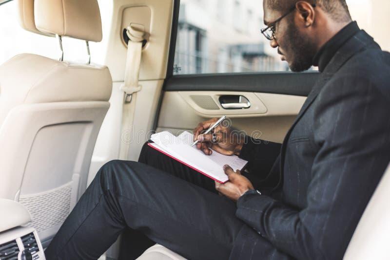 Ένα νέο επιχειρησιακό άτομο σε ένα κοστούμι κάθεται στη πίσω θέση ενός ακριβού αυτοκινήτου με ένα σημειωματάριο Επιχειρησιακές δι στοκ φωτογραφία με δικαίωμα ελεύθερης χρήσης
