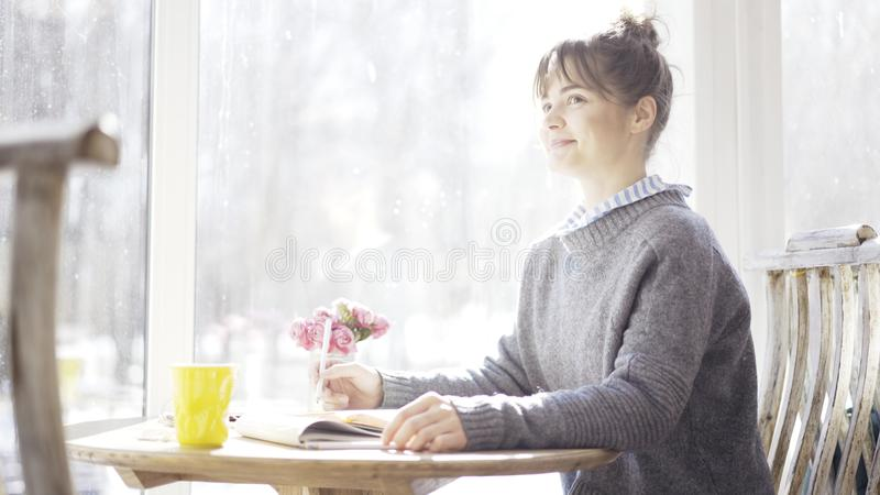 Ένα νέο ευτυχές κορίτσι brunette χαμογελά σε κάποιο σε έναν καφέ στοκ εικόνες με δικαίωμα ελεύθερης χρήσης