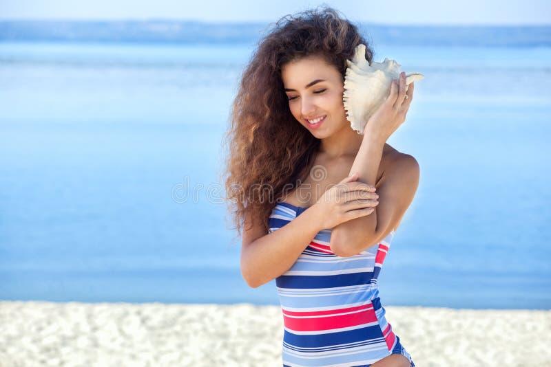 Ένα νέο ελκυστικό κορίτσι σε ένα ζωηρόχρωμο ριγωτό μαγιό κρατά ένα μεγάλο, άσπρο κοχύλι στοκ εικόνες