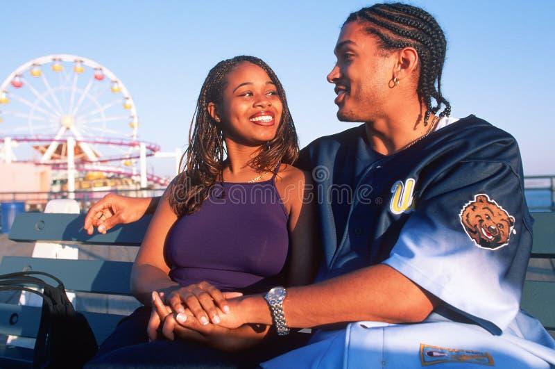 Ένα νέο ζεύγος αφροαμερικάνων ερωτευμένο στο Santa Monica Pier, ασβέστιο στοκ φωτογραφία