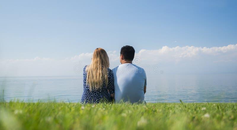 Ένα νέο ζεύγος κάθεται σε έναν πράσινο χορτοτάπητα σε μια γραφική θέση κοντά στη λίμνη στοκ φωτογραφία με δικαίωμα ελεύθερης χρήσης