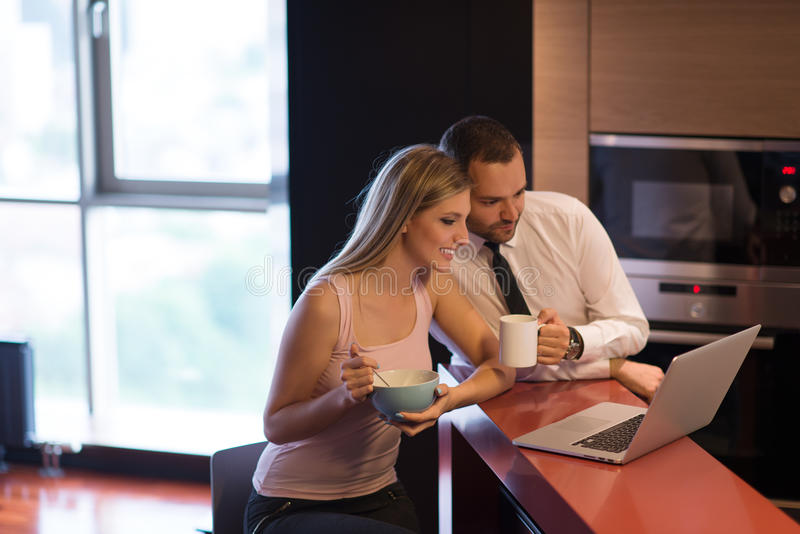 Ένα νέο ζεύγος προετοιμάζεται για μια εργασία και χρησιμοποιεί ένα lap-top στοκ φωτογραφίες