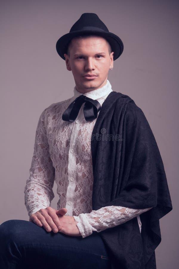 Ένα νέο καυκάσιο άτομο, ομοφυλοφιλικός gentelman, που φορά το πουκάμισο δαντελλών, καπέλο, στοκ φωτογραφία