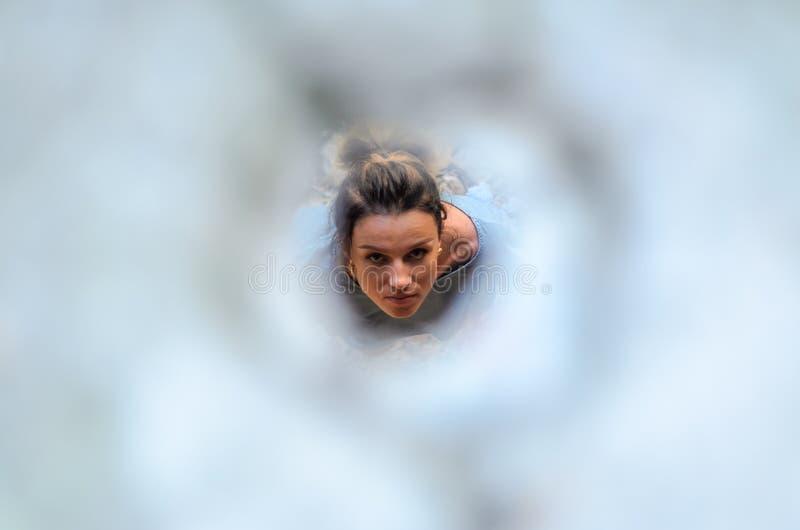 Ένα νέο κορίτσι ανατρέχει μέσω της τρύπας στοκ εικόνες με δικαίωμα ελεύθερης χρήσης