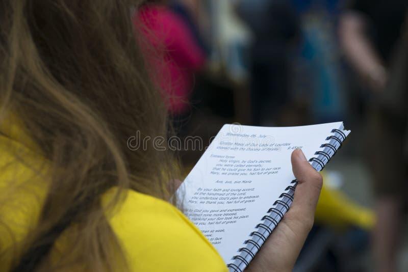 Ένα νέο κορίτσι διαβάζει ένα βιβλίο των θρησκευτικών τραγουδιών στοκ εικόνα