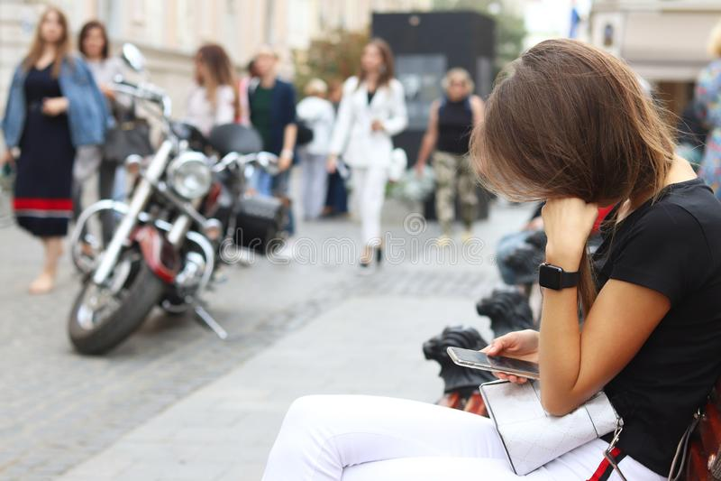 Ένα νέο κορίτσι εξετάζει ένα smartphone που κρατά Μια γυναίκα κάθεται σε έναν πάγκο στο κέντρο μιας αρχαίας πόλης ενάντια σε μια  στοκ εικόνα