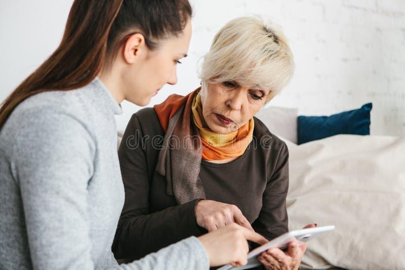 Ένα νέο κορίτσι εξηγεί σε μια ηλικιωμένη γυναίκα πώς να χρησιμοποιήσει μια ταμπλέτα ή παρουσιάζει κάποια εφαρμογή ή σας διδάσκει  στοκ φωτογραφίες