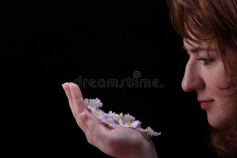 Ένα νέο κορίτσι θαυμάζει τα λουλούδια ιώδους Saintpaulia στο φοίνικα Έννοια φροντίδας δέρματος στοκ εικόνες