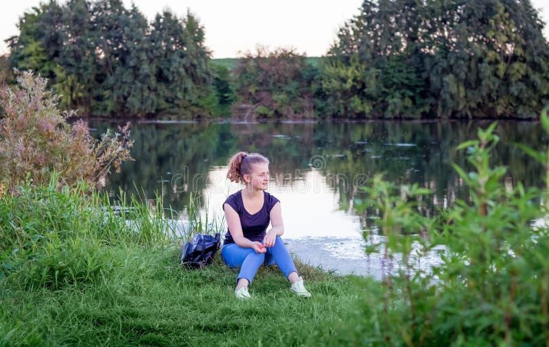 Ένα νέο κορίτσι θαυμάζει τη φύση κατά τη διάρκεια του ηλιοβασιλέματος Υγιής τρόπος ζωής στοκ εικόνες