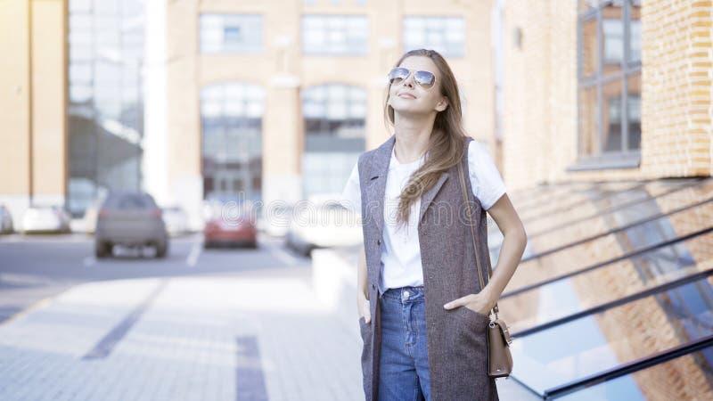 Ένα νέο κορίτσι κρατά το εξωτερικό ότι γυαλιών ηλίου παραδίδει τις τσέπες στοκ φωτογραφίες