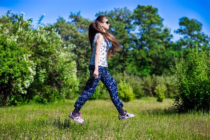 Ένα νέο κορίτσι με μακρυμάλλη στα γυαλιά ηλίου περπατά μέσω του αέρα, μετεωρισμός στοκ φωτογραφία με δικαίωμα ελεύθερης χρήσης