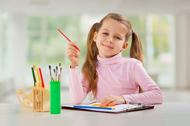 Ένα νέο κορίτσι με τη συνεδρίαση μολυβιών στον πίνακα στοκ φωτογραφία με δικαίωμα ελεύθερης χρήσης