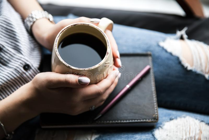 Ένα νέο κορίτσι με ένα όμορφο μανικιούρ κρατά ένα βιβλίο με ένα φλιτζάνι του καφέ προκλητική γυναίκα ύφους μόδας προσώπου μαυρισμ στοκ φωτογραφία με δικαίωμα ελεύθερης χρήσης