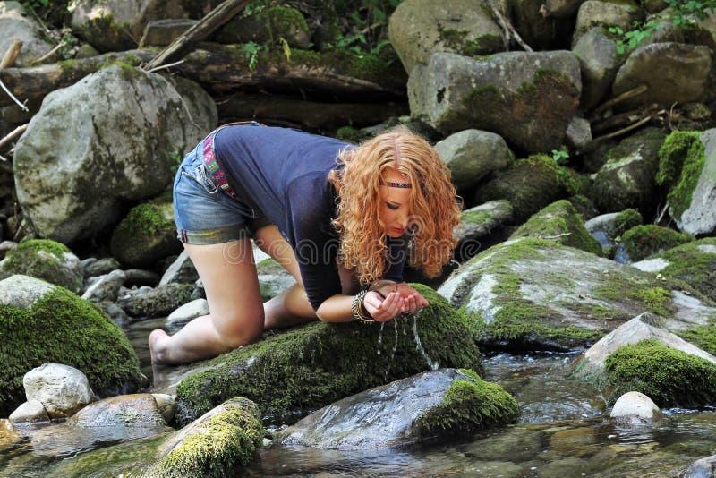 Ένα νέο κορίτσι πίνει το φρέσκο σαφές νερό στοκ φωτογραφία