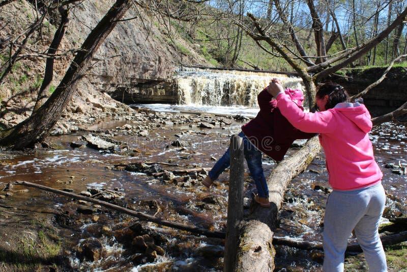 Ένα νέο κορίτσι περπατά με το παιδί της στον καταρράκτη στοκ εικόνα