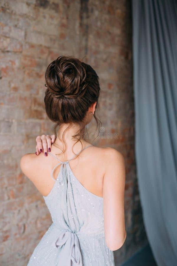 Ένα νέο κορίτσι πολυτελή σε έναν γκρίζο, - ασήμι, σπινθήρισμα, που εξισώνει την τοποθέτηση φορεμάτων στη κάμερα Μοντέρνη νύφη στο στοκ εικόνες