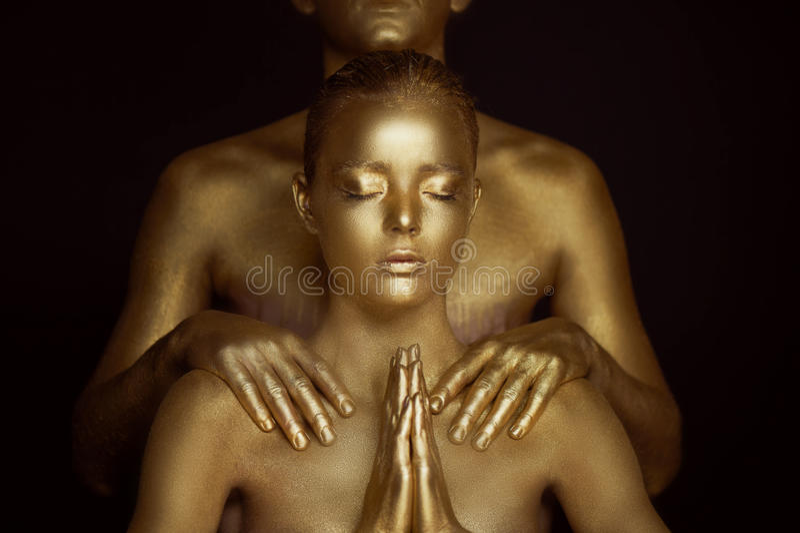 Ένα νέο κορίτσι, που καλύπτεται στο χρυσό χρώμα Τα χέρια είναι στη βουδιστική προσευχή Ικεσία, αίτημα στους ώμους στοκ εικόνα