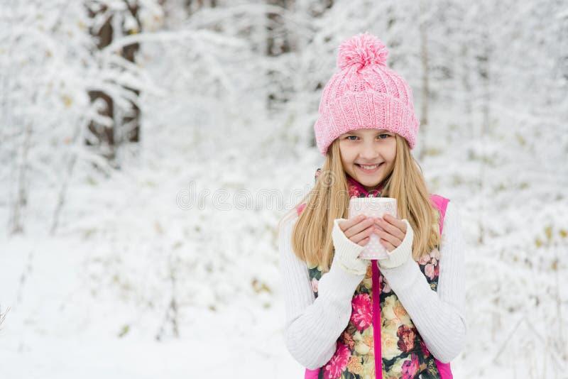 Ένα νέο κορίτσι που κρατά ένα φλυτζάνι του ζεστού ποτού και του χαμόγελου στοκ εικόνα