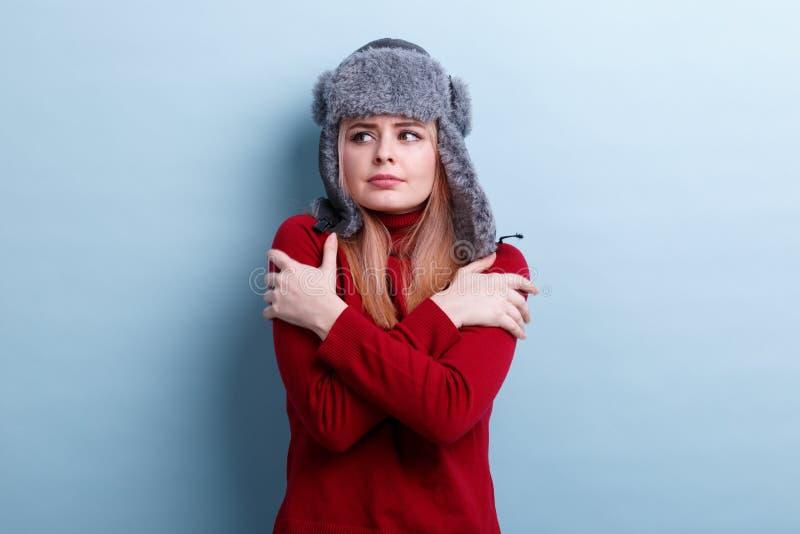 Ένα νέο κορίτσι που ντύνεται σε ένα θερμά καπέλο και ένα πουλόβερ, στέκεται και διατηρεί τους ώμους που παρουσιάζουν το κρύο στοκ εικόνα
