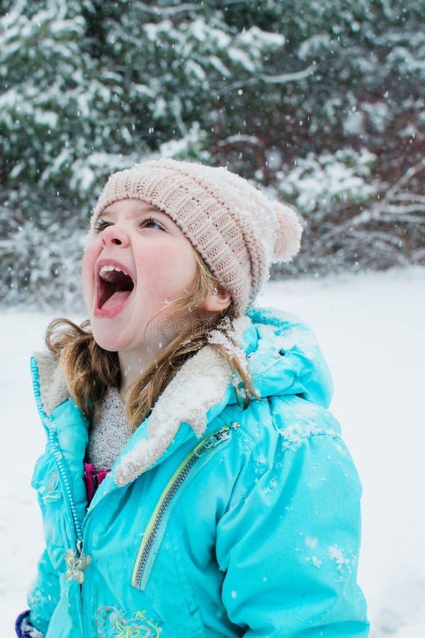 Ένα νέο κορίτσι που πιάνει snowflakes στη γλώσσα της στοκ φωτογραφία με δικαίωμα ελεύθερης χρήσης