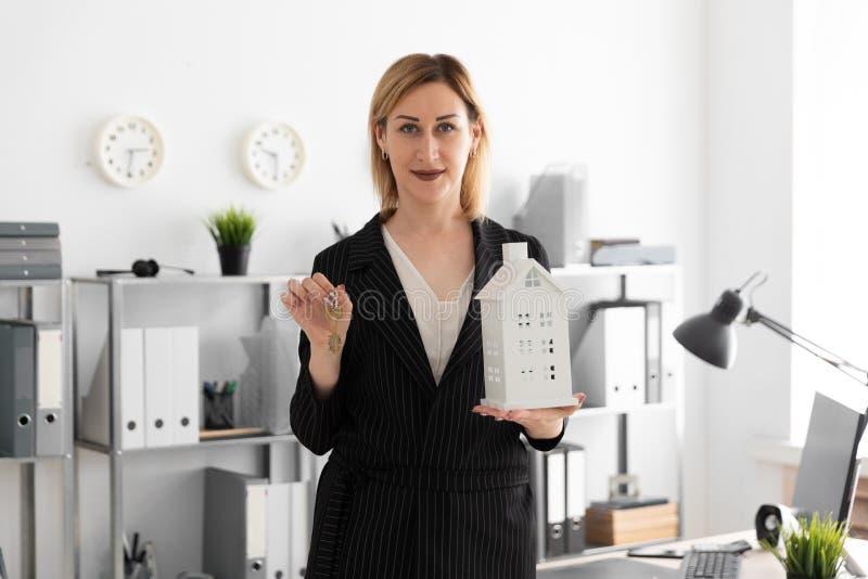 Ένα νέο κορίτσι που στέκεται στο γραφείο και που κρατά τα κλειδιά και το σχεδιάγραμμα του σπιτιού στοκ εικόνες