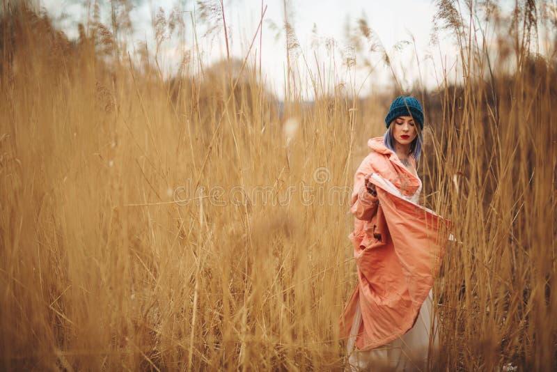 Ένα νέο κορίτσι που φορά ένα παλτό κρητιδογραφιών και ένα μοντέρνο καπέλο θέτει σε έναν τομέα σίτου στοκ εικόνα