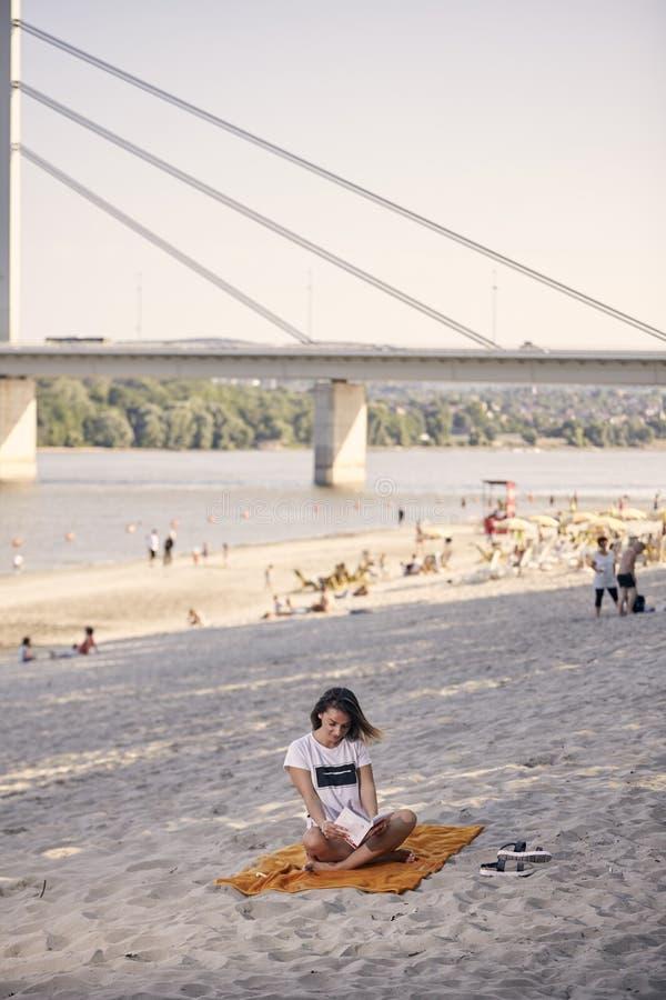Ένα νέο κορίτσι, που χαλαρώνει διαβάζοντας ένα βιβλίο υπαίθρια, παραλία στοκ εικόνα