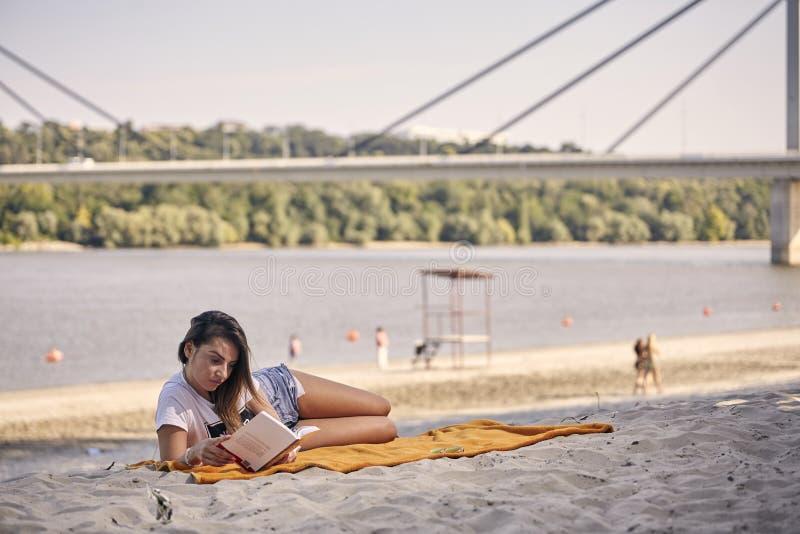 Ένα νέο κορίτσι, που χαλαρώνει διαβάζοντας ένα βιβλίο υπαίθρια, περιστασιακά ενδύματα στοκ εικόνες