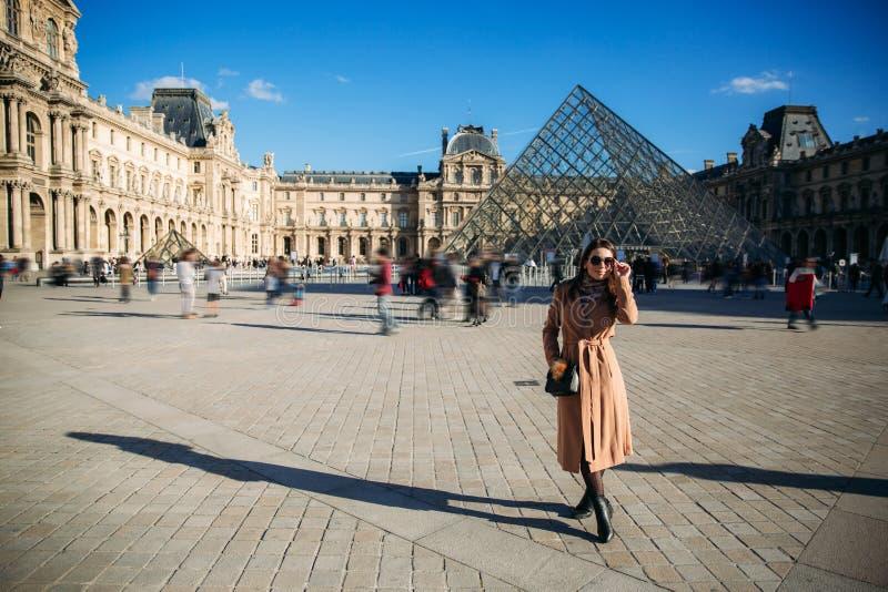 Ένα νέο κορίτσι σε ένα καφετιά παλτό και ένα μαντίλι στέκεται στο υπόβαθρο της πόλης Παρίσι Το φθινόπωρο έχει ήλιο τον καιρό, του στοκ φωτογραφία