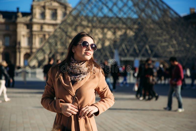 Ένα νέο κορίτσι σε ένα καφετιά παλτό και ένα μαντίλι στέκεται στο υπόβαθρο της πόλης Παρίσι Το φθινόπωρο έχει ήλιο τον καιρό, του στοκ φωτογραφίες