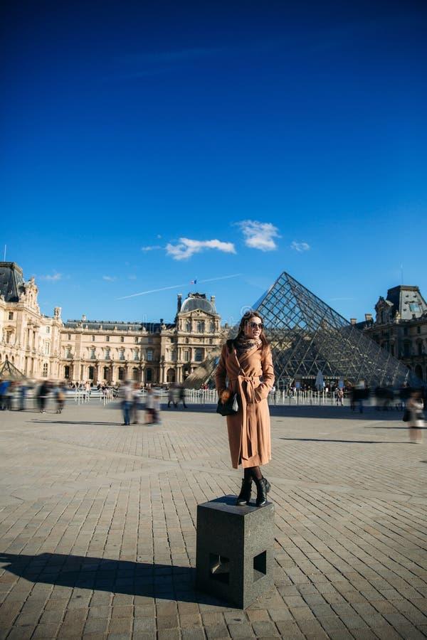 Ένα νέο κορίτσι σε ένα καφετιά παλτό και ένα μαντίλι στέκεται στο υπόβαθρο της πόλης Παρίσι Το φθινόπωρο έχει ήλιο τον καιρό, του στοκ φωτογραφία με δικαίωμα ελεύθερης χρήσης