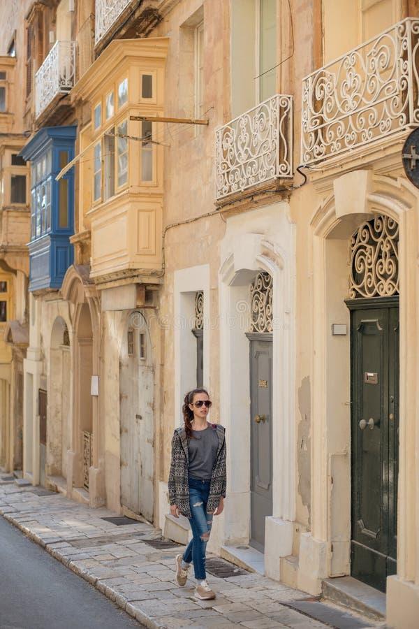 ένα νέο κορίτσι στα ενδύματα τρόπου ζωής strolling μέσω των στενών οδών μιας αρχαίας πόλης με τις παλαιά πόρτες και τα μπαλκόνια στοκ φωτογραφία