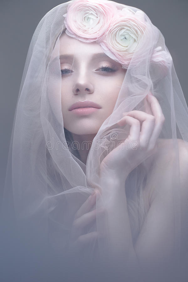Ένα νέο κορίτσι στην εικόνα μιας νύφης με ένα πέπλο στο πρόσωπό της Όμορφο πρότυπο με ένα στεφάνι των λουλουδιών στο κεφάλι της στοκ εικόνες