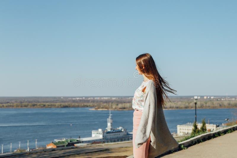 Ένα νέο κορίτσι στο ανάχωμα ενός μεγάλου ποταμού, που εξετάζει το νερό στοκ φωτογραφία