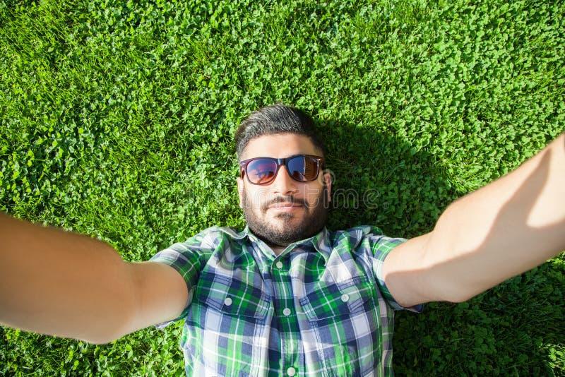 Ένα νέο Μεσο-Ανατολικό άτομο μόδας με τη γενειάδα και το ύφος τρίχας μόδας βρίσκεται σε μια χλόη σε ένα πάρκο που παίρνει selfie στοκ εικόνες