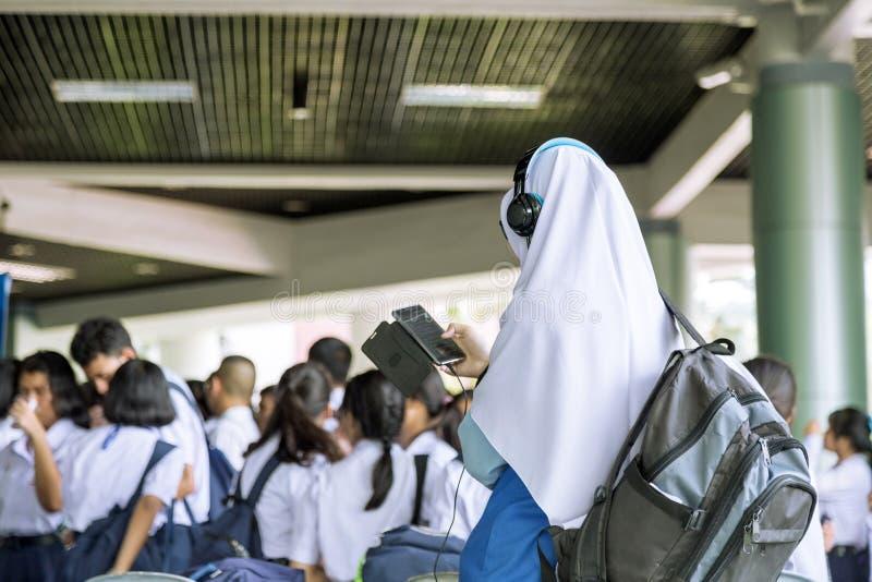 Ένα νέο μουσουλμανικό κορίτσι που ακούει τη μουσική από το τηλέφωνό της στοκ φωτογραφίες