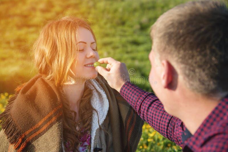 Ένα νέο παντρεμένο ζευγάρι σε ένα πικ-νίκ ταΐζει το ένα το άλλο με μια σύριγγα στοκ φωτογραφίες με δικαίωμα ελεύθερης χρήσης