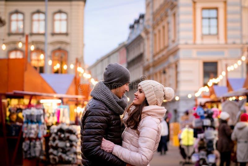 Ένα νέο ρομαντικό ζεύγος που φορά τα χειμερινά ενδύματα που αγκαλιάζουν στεμένος στην οδό βραδιού με την έκθεση Χριστουγέννων στοκ εικόνες με δικαίωμα ελεύθερης χρήσης