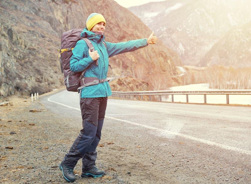 Ένα νέο χαμογελώντας κορίτσι ταξιδεύει στα βουνά σταματά το ασβέστιο στοκ φωτογραφία με δικαίωμα ελεύθερης χρήσης