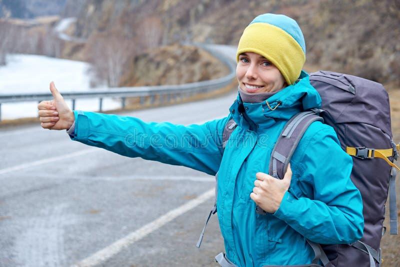 Ένα νέο χαμογελώντας κορίτσι ταξιδεύει στα βουνά σταματά το αυτοκίνητο στο δρόμο κάνοντας ωτοστόπ, αυξάνει το χέρι του στοκ εικόνες