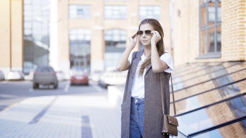 Ένα νέο χαμογελώντας κορίτσι φορά τα γυαλιά ηλίου έξω στοκ φωτογραφίες με δικαίωμα ελεύθερης χρήσης