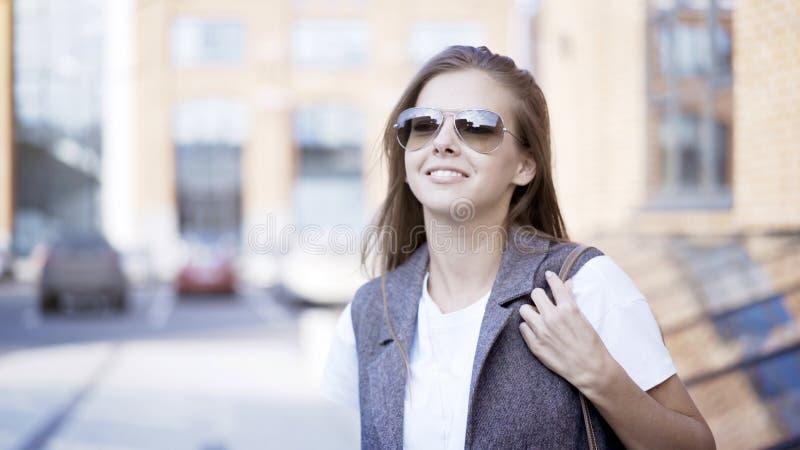 Ένα νέο χαμογελώντας κορίτσι φορά τα γυαλιά υπαίθρια στοκ φωτογραφίες με δικαίωμα ελεύθερης χρήσης